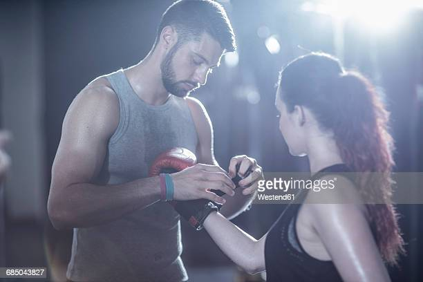 Coach helping female boxer putting on boxing gloves