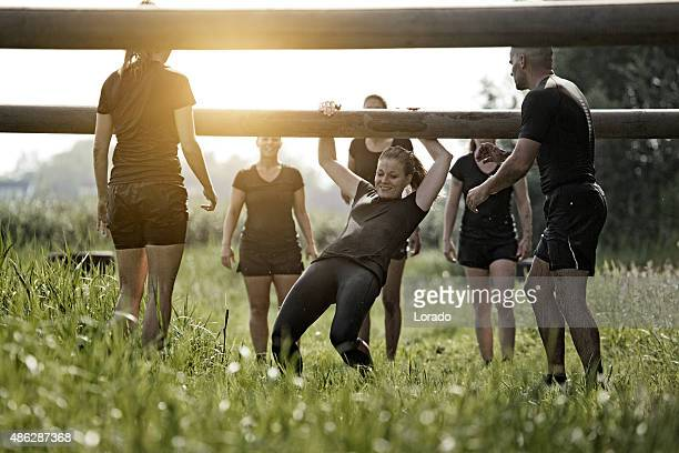 coach helping group of women to cross wooden obstacle