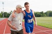 Coach helping runner after race