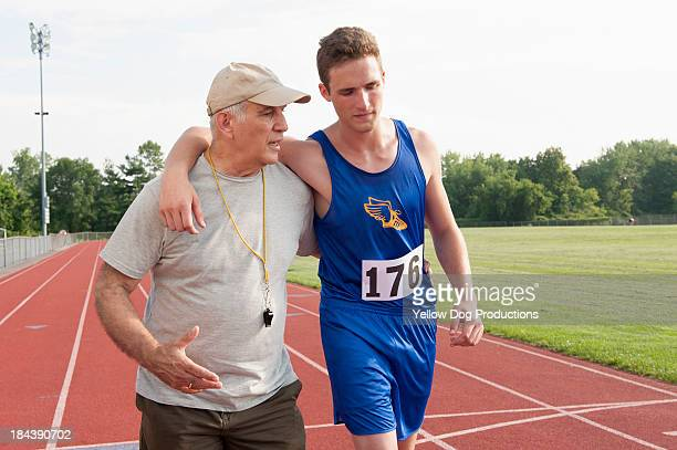 Coach helping runner after race