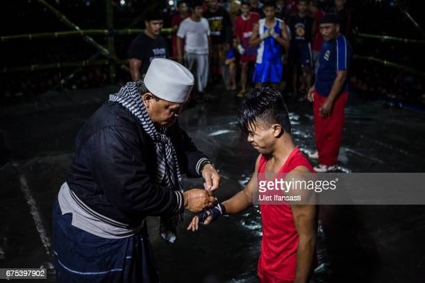 A coach helps wrap his student hand during the Pencak Dor competition at the yard of Lirboyo islamic boarding school on April 29 2017 in Kediri East...