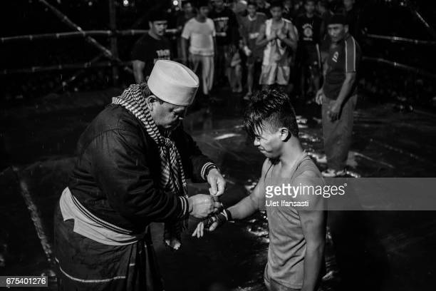A coach helps wrap his student's hand during Pencak Dor competition at the yard of Lirboyo islamic boarding school on April 29 2017 in Kediri East...