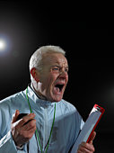 Coach holding clipboard, screaming, close-up