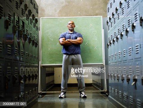 Coach in locker room, standing in front of chalkboard
