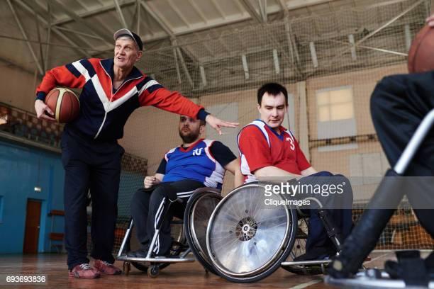 Coach instructing adaptive basketball players