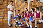 Coach interacting with basketball players in the court