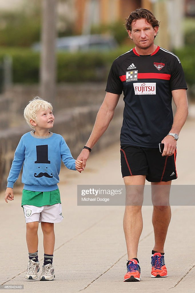 Coach James Hird walks with his son Alexander Hird during an Essendon Bombers AFL mini triathlon training session at Williamstown Beach on January 24...