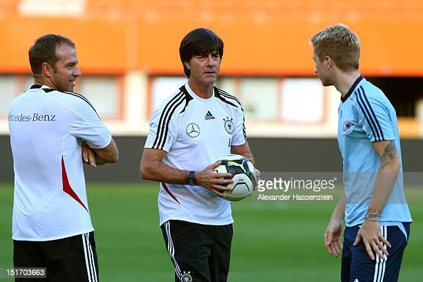 Coach Joachim Loew of Germany and assistent coach Hansi Flick talk to Marco Reus during a training session on the eve of their FIFA World Cup Brazil...