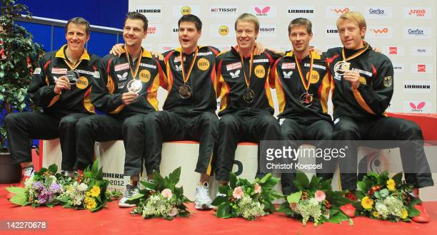 Coach Joerg Rosskopf Timo Boll Dimitrij Ovtcharov Patrick Baum Bastian Steger and Christian Suess of Germany present their silver medal during the...
