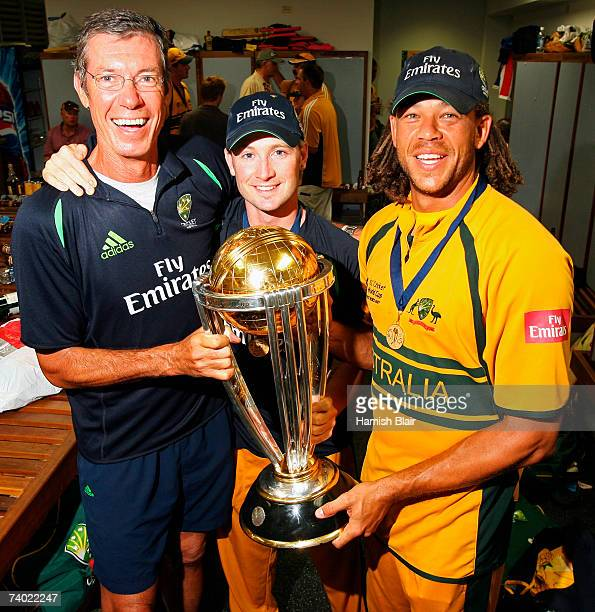 Coach John Buchanan Michael Clarke and Andrew Symonds of Australia hold the ICC World Cup trophy in the changing rooms after the ICC Cricket World...