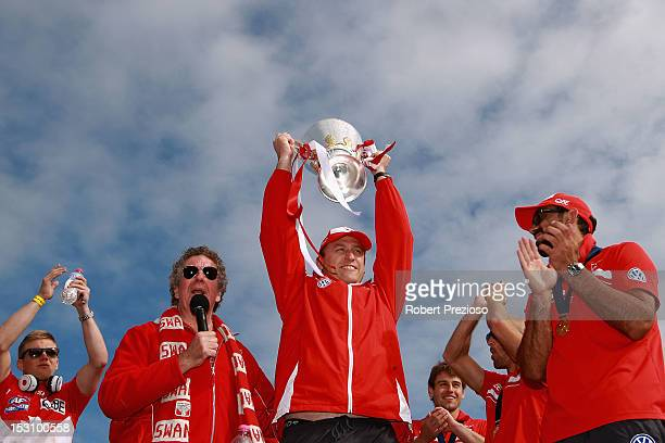 Coach John Longmire holds the Premiership Cup aloft as Swans players are presented to supporters at Lakeside Stadium during a Sydney Swans official...