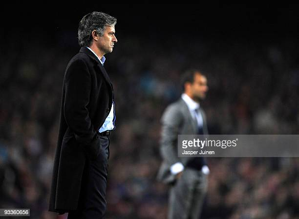 Coach Jose Mourinho of Inter Milan follows his players backdropped by coach Josep Guardiola of FC Barcelona during the UEFA Champions League group F...