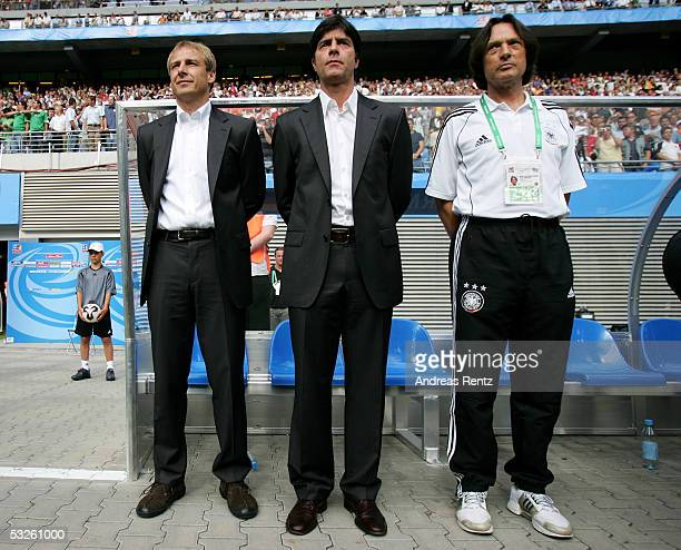Coach Juergen Klinsmann and Assistant Coach Joachim Loew and Doctor Hans Wilhelm Mueller Wohlfahrt of Germany looks on during the game between...