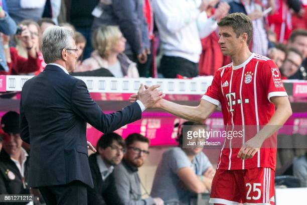 Coach Jupp Heynckes of Muenchen shakes hands with Thomas Mueller of Bayern Muenchen who is being substituted during the Bundesliga match between FC...