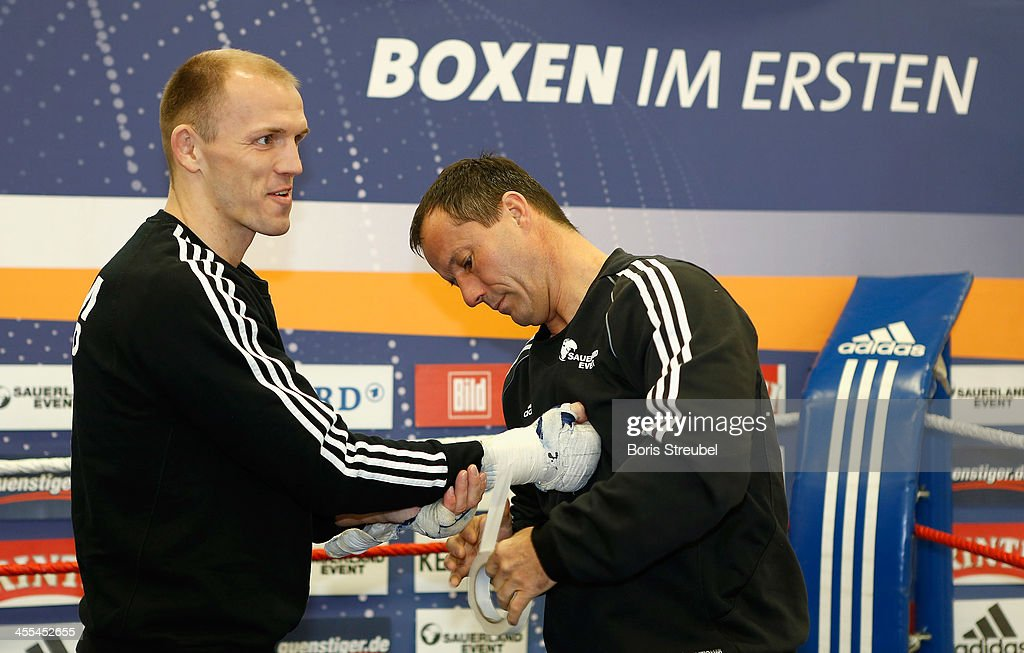Coach Karsten Roewer bandage the hands of light heavyweight fighter Juergen Braehmer (L) prior to a public trainig session at Sporthalle Binsenwerder on December 12, 2013 in Neubrandenburg, Germany.
