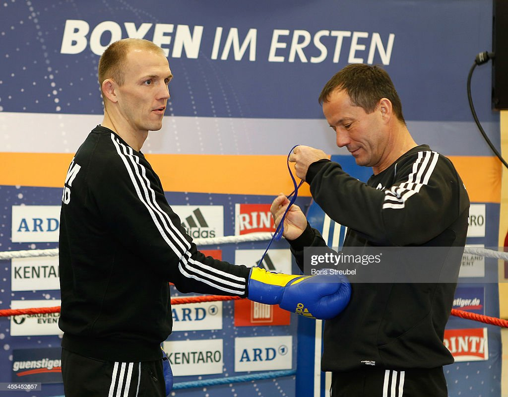 Coach Karsten Roewer laces the boxing gloves of light heavyweight fighter <a gi-track='captionPersonalityLinkClicked' href=/galleries/search?phrase=Juergen+Braehmer&family=editorial&specificpeople=608880 ng-click='$event.stopPropagation()'>Juergen Braehmer</a> (L) during a public trainig session at Sporthalle Binsenwerder on December 12, 2013 in Neubrandenburg, Germany.