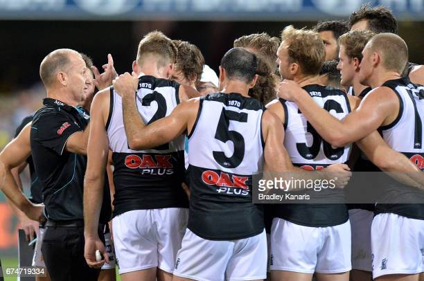 Coach Ken Hinkley of the Power talks tactics to his players at the 3rd quarter break during the round six AFL match between the Brisbane Lions and...