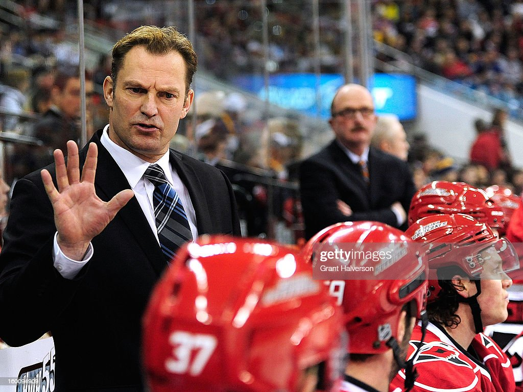 Coach Kirk Mueller of the Carolina Hurricanes talks with his team during the first period against the Buffalo Sabres during play at PNC Arena on January 24, 2013 in Raleigh, North Carolina.