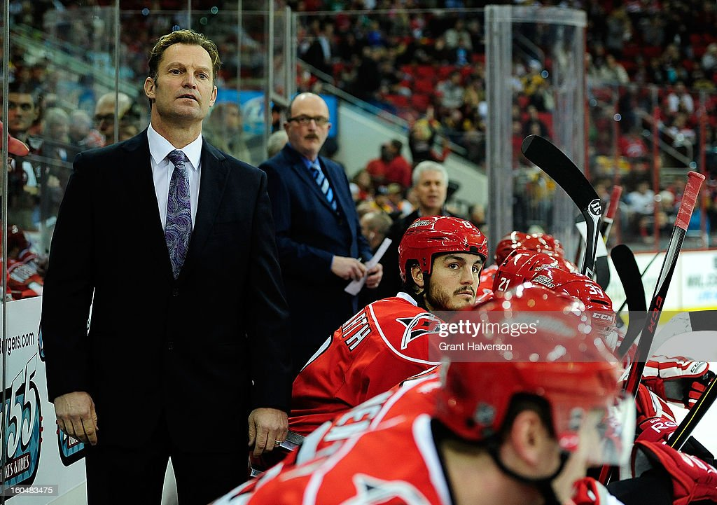 Coach Kirk Mueller of the Carolina Hurricanes watches his team during the game against the Boston Bruins at PNC Arena on January 28, 2013 in Raleigh, North Carolina.