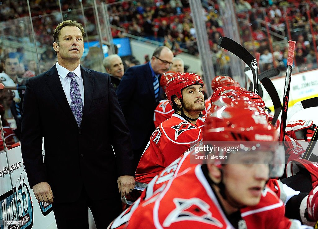 Coach Kirk Mueller of the Carolina Hurricanes watches his team in action against the Boston Bruins at PNC Arena on January 28, 2013 in Raleigh, North Carolina.