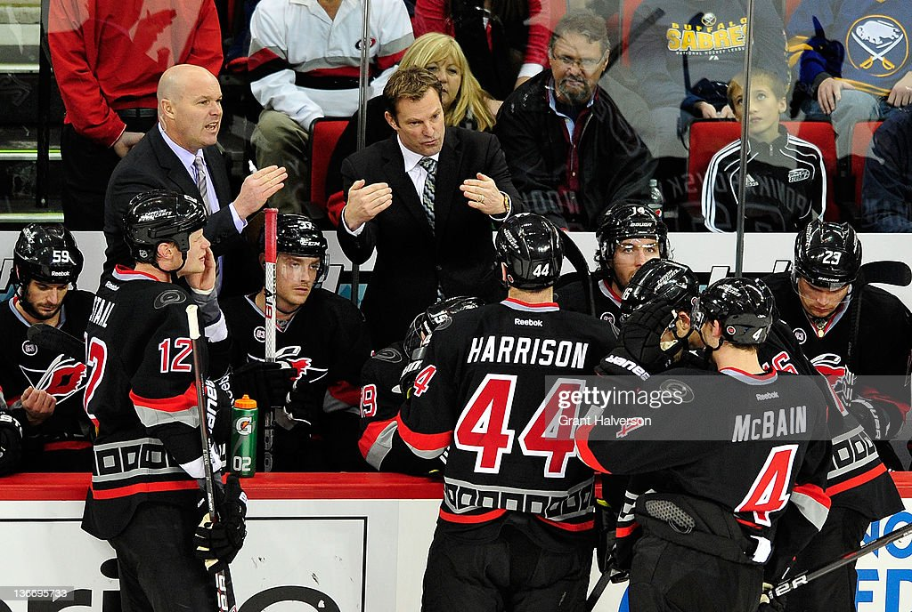 Coach Kirk Muller of the Carolina Hurricanes huddles with his team against the Buffalo Sabres during play at the RBC Center on January 6, 2012 in Raleigh, North Carolina. The Hurricanes won 4-2.