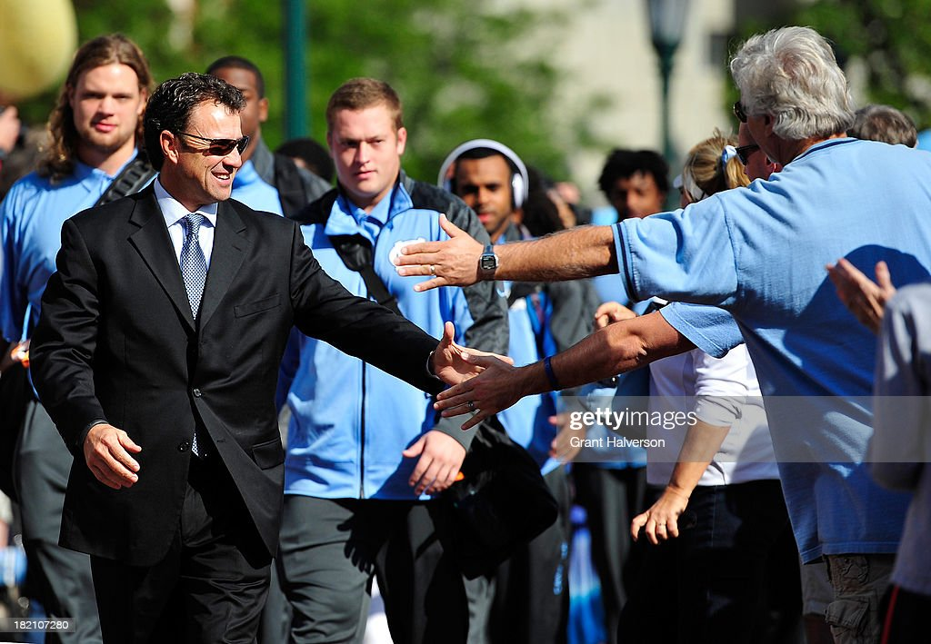 Coach Larry Fedora of the North Carolina Tar Heels greets fans during the team's 'Victory Walk' before a game against the East Carolina Pirates at Kenan Stadium on September 28, 2013 in Chapel Hill, North Carolina.