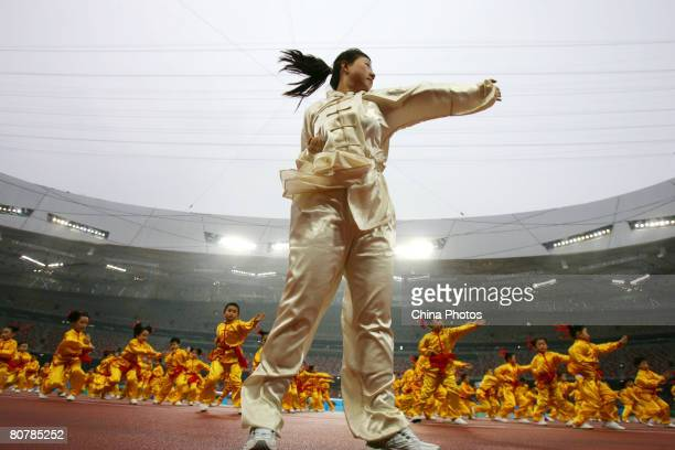 A coach leads children to perform martial arts during the 'Good Luck Beijing' 2008 Beijing International Marathon Race at the National Stadium dubbed...