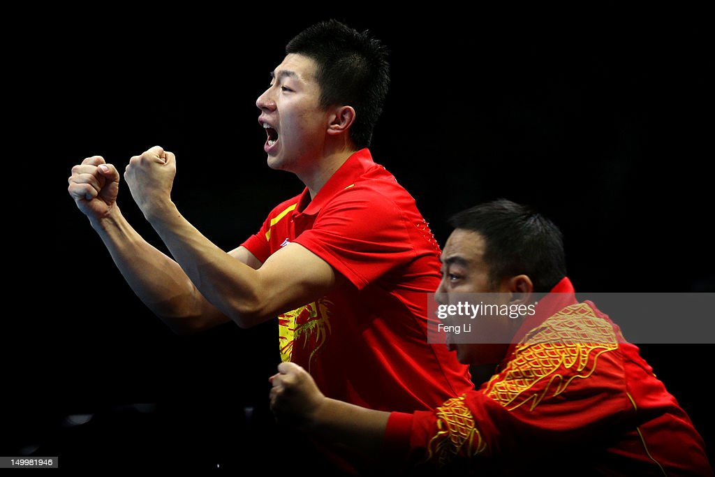 Coach <a gi-track='captionPersonalityLinkClicked' href=/galleries/search?phrase=Liu+Guoliang&family=editorial&specificpeople=655363 ng-click='$event.stopPropagation()'>Liu Guoliang</a> (R) cheers with <a gi-track='captionPersonalityLinkClicked' href=/galleries/search?phrase=Ma+Long&family=editorial&specificpeople=2158981 ng-click='$event.stopPropagation()'>Ma Long</a> (L) of China as Zhang Jike of China competes against Saehyuk Joo of Korea during the Men's Team Table Tennis gold medal match on Day 12 of the London 2012 Olympic Games at ExCeL on August 8, 2012 in London, England.