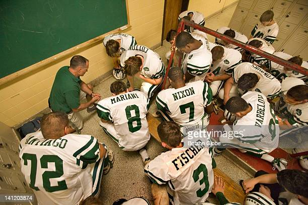 Coach Marcus Borden of East Brunswick High School takes a knee as a player says a pregame prayer in the locker room moments before a game between...