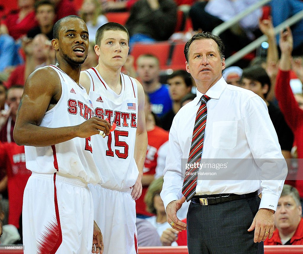 Coach Mark Gottfried huddles with Lorenzo Brown #2 and Scott Wood #15 of the North Carolina State Wolfpack during a win over the North Carolina-Asheville Bulldogs during play at PNC Arena on November 23, 2012 in Raleigh, North Carolina. North Carolina State won 82-80.