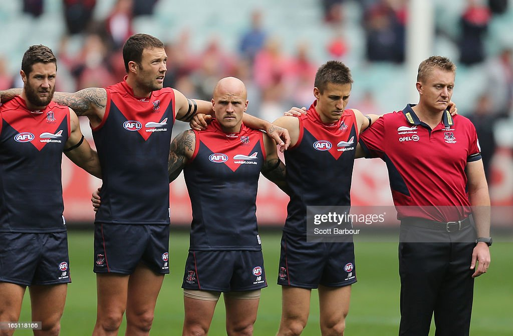 Coach Mark Neeld, Nathan Jones and Jack Grimes of the Demons stand for the national anthem before the round one AFL match between the Melbourne Demons and Port Adelaide Power at the Melbourne Cricket Ground on March 31, 2013 in Melbourne, Australia.