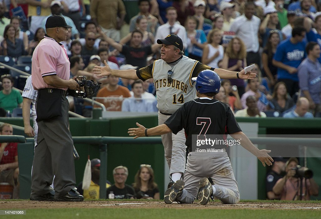 Coach Mike Doyle, D-Pa., center, and Rep. Ed Perlmutter, D-Colo., argue a call in which Perlmutter was called out at home plate during the 51st Annual CQ Roll Call Congressional Baseball Game held at Nationals Park. The Democrats prevailed over the Republicans 18-5.