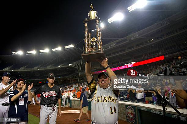 Coach Mike Doyle holds up the Roll Call trophy after the Democrats won the 52nd annual Congressional Baseball Game at National Stadium in Washington...