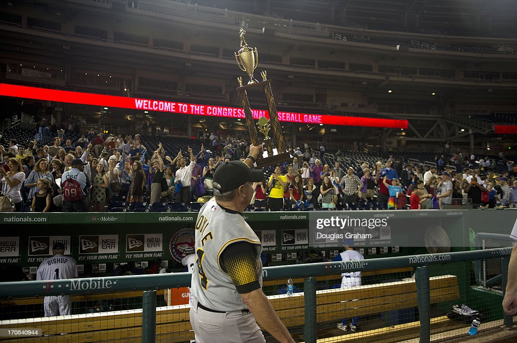 Coach Mike Doyle holds up the Roll Call trophy after the Democrats won the 52nd annual Congressional Baseball Game at National Stadium in Washington on Thursday, June 13, 2013.