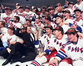 Coach Mike Keenan and New York Rangers surround the Stanley Cup on the ice at Madison Square Garden after the Rangers defeated the Vancouver Canucks...
