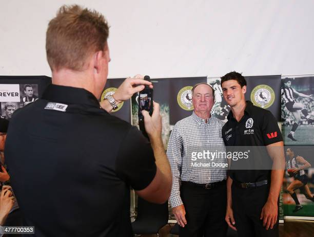 Coach Nathan Buckley takes a photo of captain Scott Pendlbury and former captain Max Richardson during the Collingwood Magpies AFL season launch at...