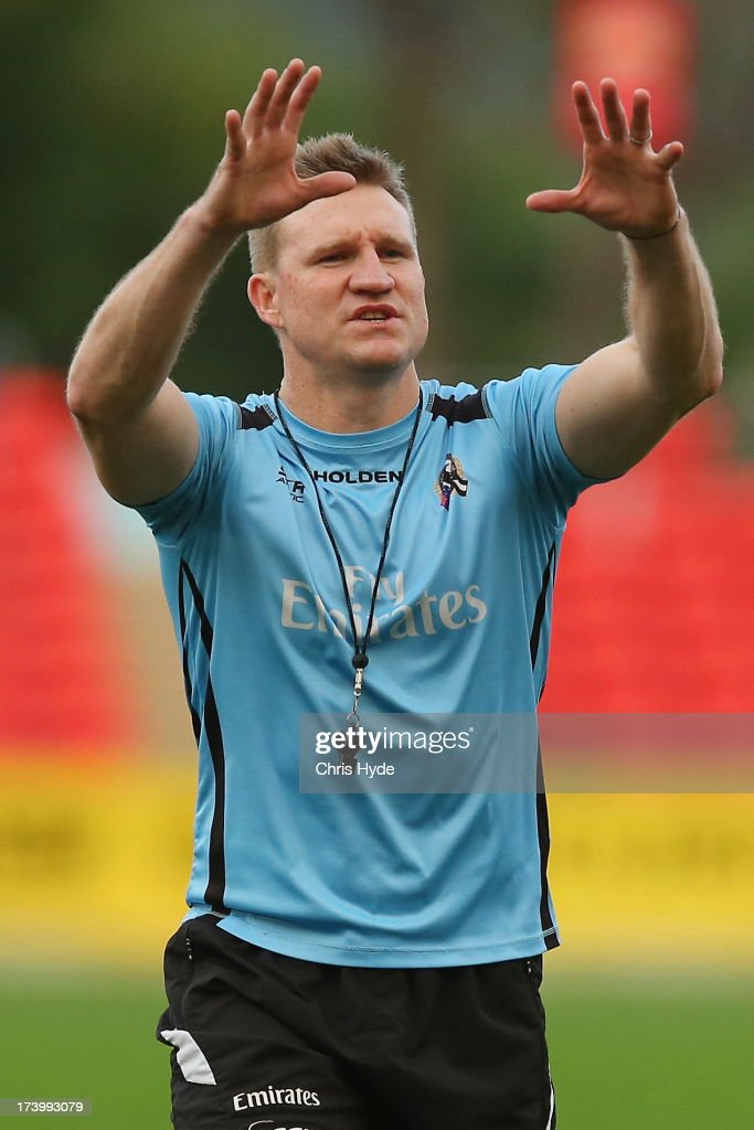 Coach Nathan Buckley talks to players during a Collingwood Magpies AFL training session at Metricon Stadium on July 19, 2013 in Gold Coast, Australia.