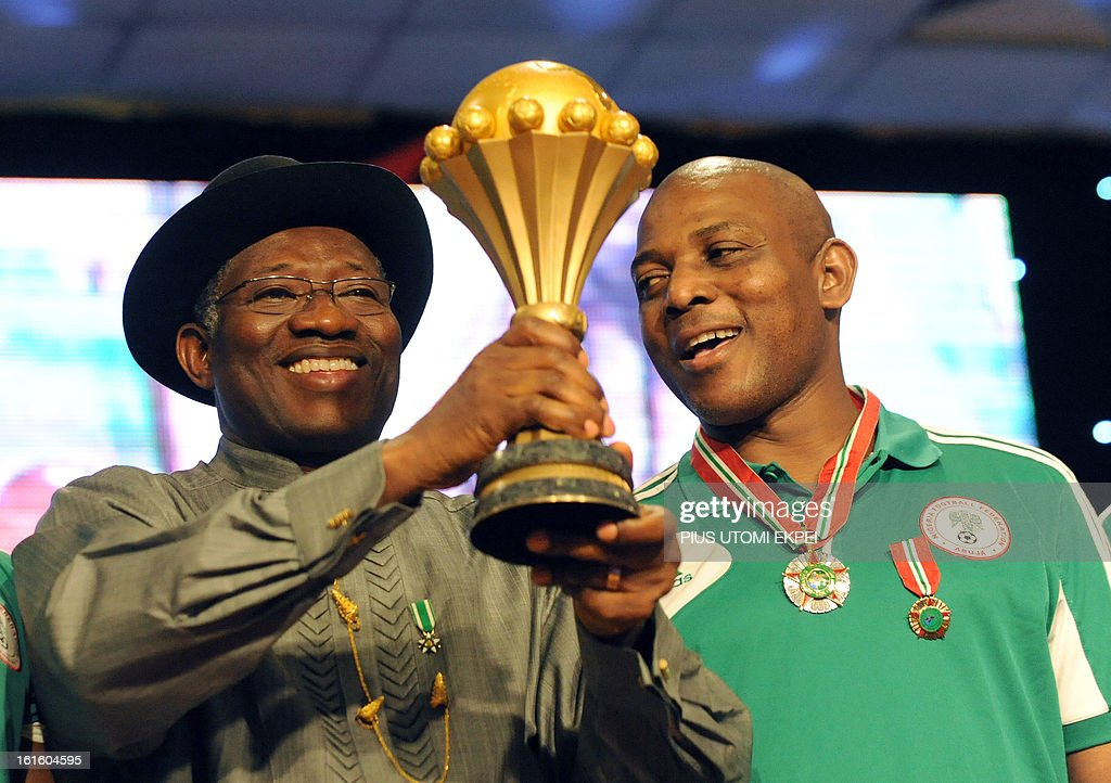 Coach of Nigerian football team Stephen Keshi (R) looks on as President Goodluck Jonathan raises the trophy won at the just concluded 2013 African Cup of Nations during the presidential banquet in honour of the victorious team in Abuja February 12, 2013. The newly crowned African champions Nigerian Super Eagles arrives in Abuja to a warm reception by fans and government officials after defeating Burkina Faso to win the 2013 African Cup of Nations in South Africa.