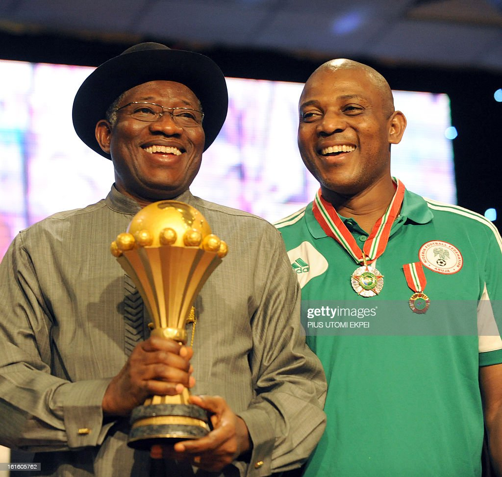 Coach of Nigerian football team Stephen Keshi (R) poses with President Goodluck Jonathan who holds the 2013 African Cup of Nations trophy during the presidential banquet in honour of the victorious national football team in Abuja February 12, 2013. The newly crowned African champions Nigerian Super Eagles arrives in Abuja to a warm reception by fans and government officials after defeating Burkina Faso to win the 2013 African Cup of Nations in South Africa.