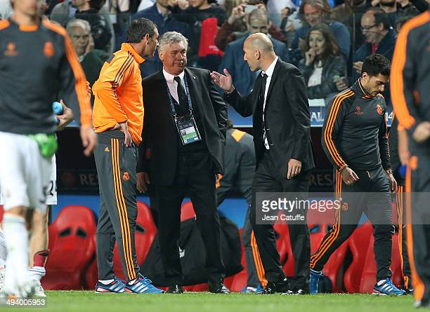 Coach of Real Madrid Carlo Ancelotti is surrounded by his assistantcoaches Paul Clement and Zinedine Zidane during the UEFA Champions League final...