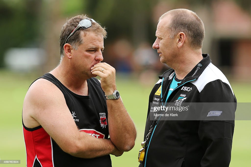 Coach of the SA Redbacks Darren Berry speaks to Coach of the Power Ken Hinkley after the two teams started their training sessions in the same area...