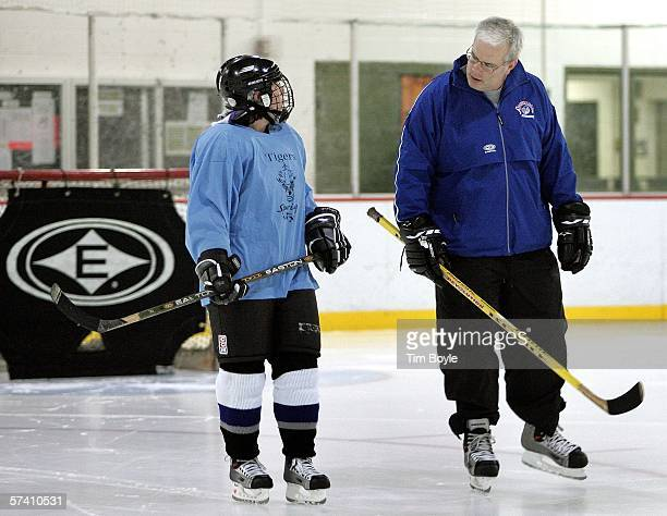 Coach of the women's ice hockey team the Jets Rich Blakey skates with team member during warmups at their morning practice April 24 2006 at The...