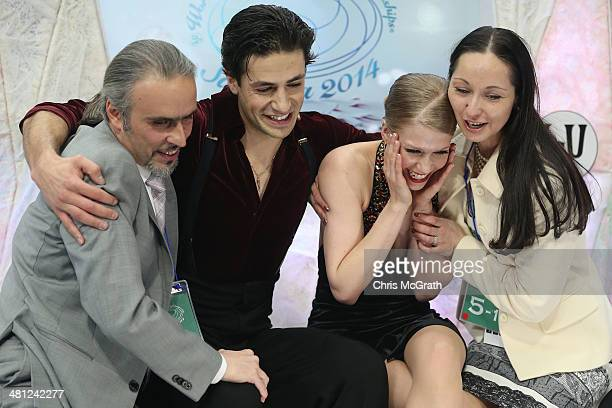 Coach Pasquale Camerlengo skaters Andrew Poje and Kaitlyn Weaver of Canada and coach Anjelika Krylova react after seeing their score in the Ice Dance...