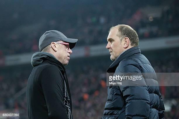Coach Peter Stoeger of Koeln and sport director Joerg Schmadtke of Koeln talk prior to the Bundesliga match between 1 FC Koeln and Bayer 04...