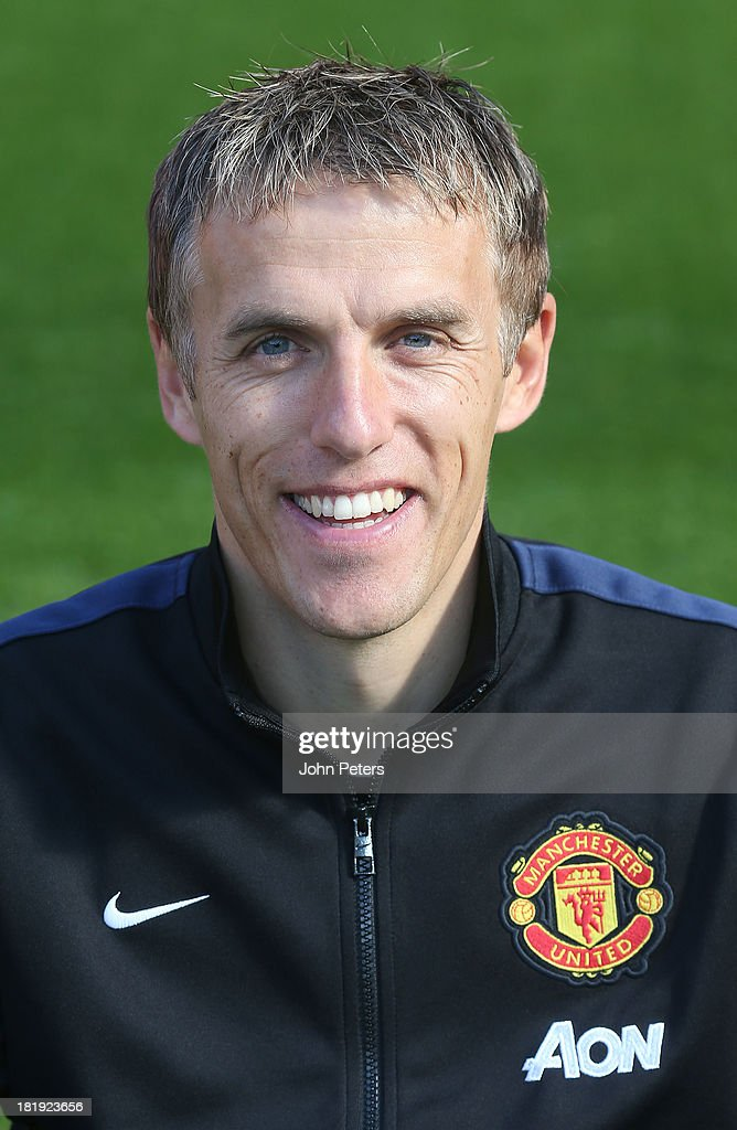 Coach Phil Neville of Manchester Unted poses at the annual club photocall at Old Trafford on September 26, 2013 in Manchester, England.