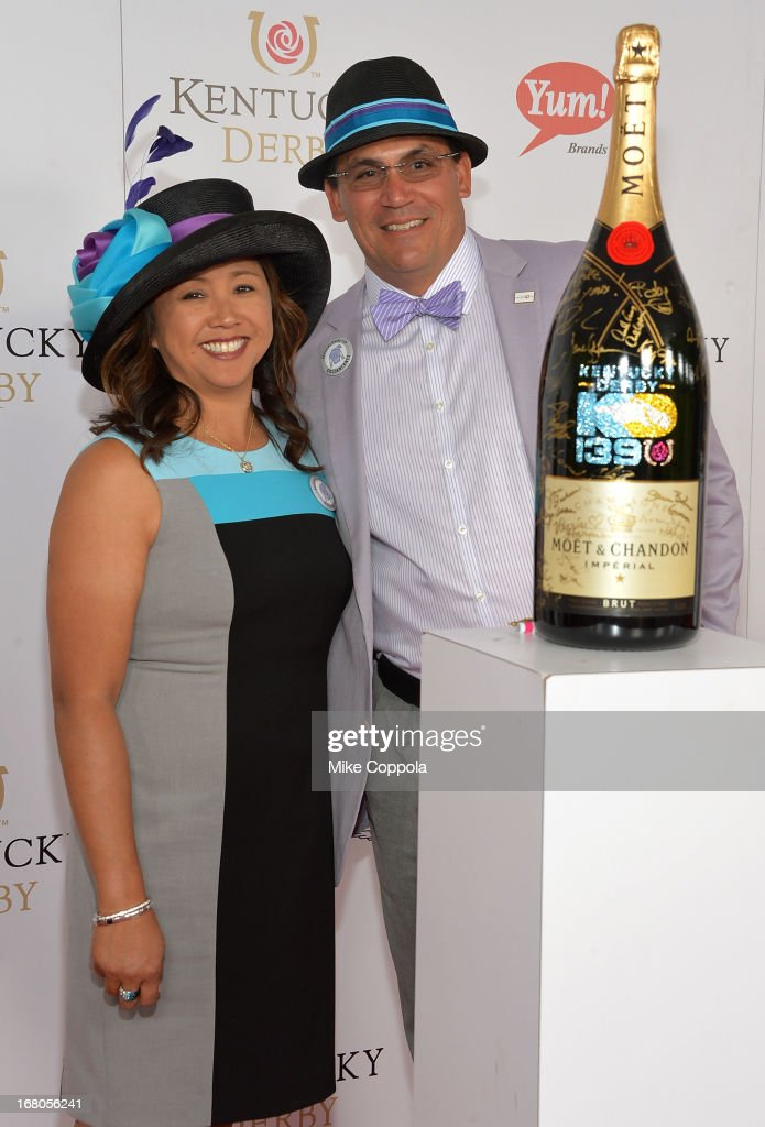 Coach Ron Rivera and Stephanie Rivera sign the Moet Chandon 6L for the Churchill Downs Foundation during the 139th Kentucky Derby at Churchill Downs...
