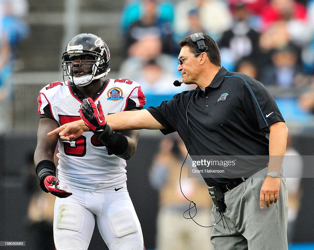 Coach Ron Rivera of the Carolina Panthers tangles with Stephen Nichols #54 of the Atlanta Falcons as he throws a challenge flag during play at Bank of America Stadium on December 9, 2012 in Charlotte, North Carolina. Carolina defeated Atlanta, 30-20.