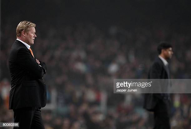 Coach Ronald Koeman of Valencia looks at his players backdropped by his fellow countryman coach Frank Rijkaard of Barcelona during the Copa del Rey...