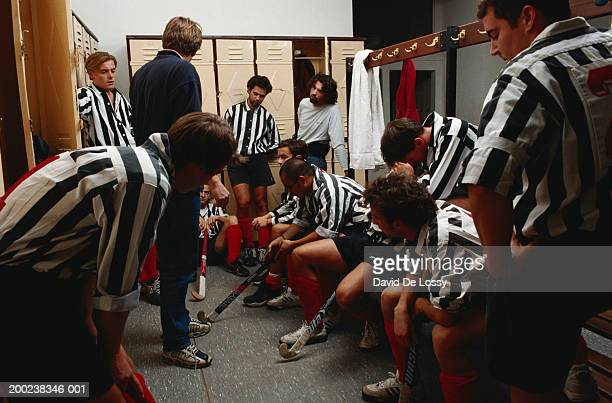Coach shouting at hockey players in locker room