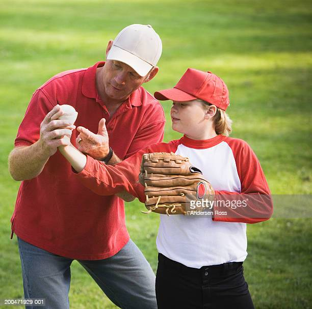 Coach showing boy (9-11) how to hold baseball